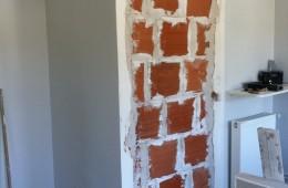 Condamnation d'une porte sur une cloison en briques.